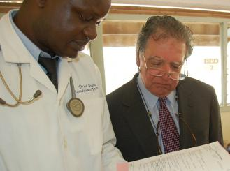 Dr. Comis and a Ugandan physician look at a patient chart