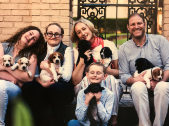 Dr. Patt with her family and a few of the 12 dogs they fostered last summer.