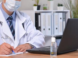 Doctor on computer with mask