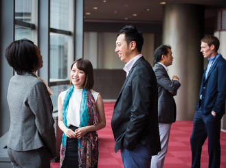 Stock image of people talking at a conference