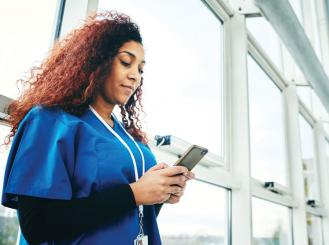 A physician looks at her smartphone