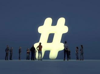 crowd gathered around a super-sized hashtag