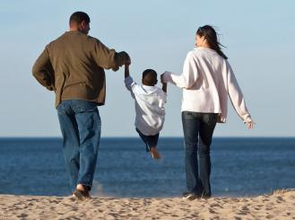 Stock image of mother and father holding child on a beach