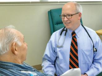 Photo of Dr. David M. Waterhouse with an elderly male patient