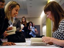 "Dr. Lucy Kalanithi (right) signs a copy of ""When Breath Becomes Air"" for Andrea M. Ferrian, MD, during the ASCO Book Club session at the 2016 ASCO Annual Meeting"