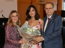Dr. Nagi S. El Saghir (right) and Ms. Mirna A. Sabbah Hoballah (left) present a bouquet of flowers to Miss Lebanon Nadine N. Njeim (center).