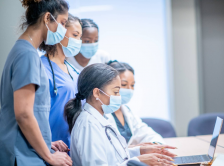 Women physicians of color collaborating around a computer