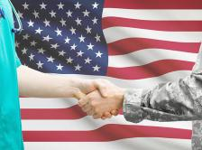 A physician and veteran shake hands in front of an American flag.