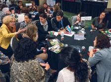 Photo of faculty and attendees discussing topics in oncology and cancer survivorship during meet the faculty networking roundtables at the 2016 Cancer Survivorship Symposium