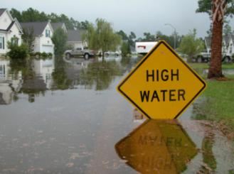 """a flooded street and a """"high water"""" warning sign"""