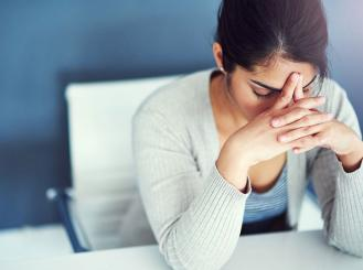 Stock image of woman with hands folded against her forehead